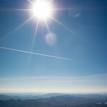 Sun and contrail from atop Mount Marcy, Adirondack Park New York.